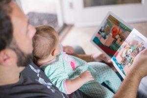Баща чете приказка на бебе